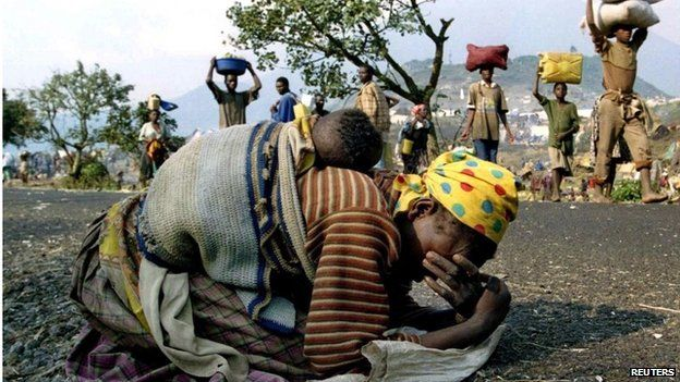 A Rwandan woman collapses with her baby on her back alongside the road connecting Kibumba refugee camp in 1994