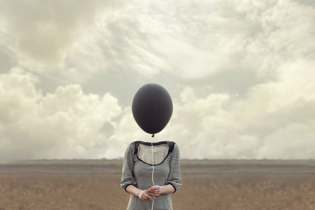 Photo of a woman on an open field, but the woman's head has been replaced by a black balloon, and the feeling is eery