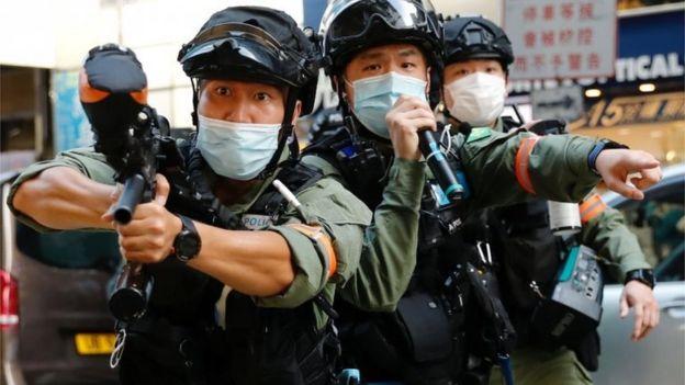 警方多次举起胡椒枪警告。