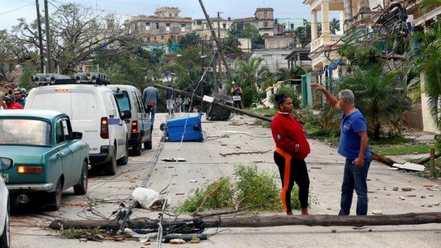 Neighbours in Havana talk with debris strewn in streets around them
