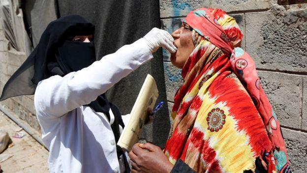 Una mujer vacuna a otra mujer mayor contra el cólera en Yemen en 2019