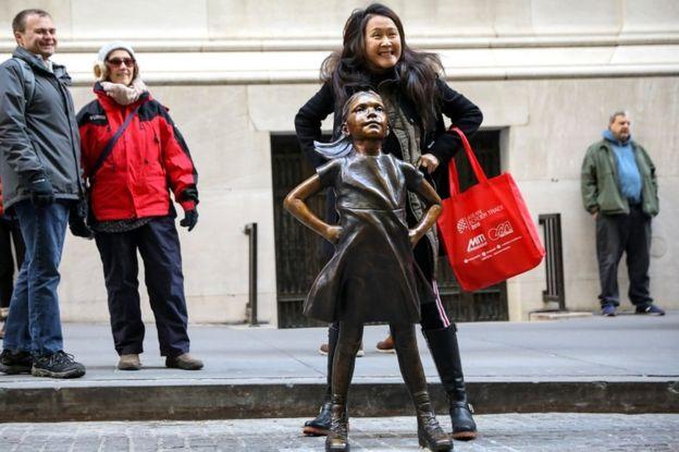 ده دسامبر 2018، یک زن با مجسمه دختر شجاع عکس میگیرد