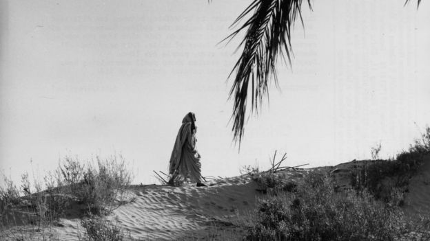 Mujer beduina camina por el Sahara.