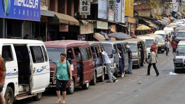 Microbuses privados esperan a los brasileños que van a comprar a Ciudad del Este, en Paraguay.