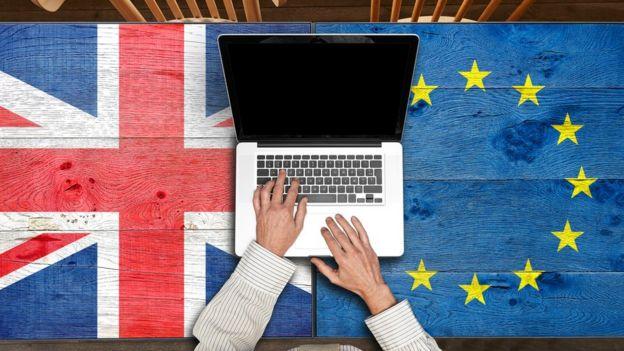 Laptop sobre banderas de Reino Unido y de la UE