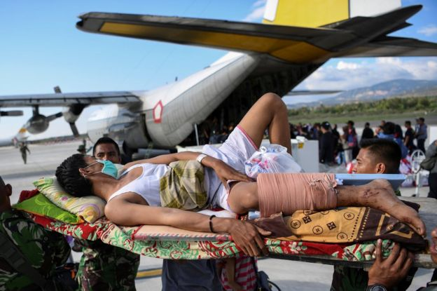 An injured man awaits evacuation at Palu airport, 30 September