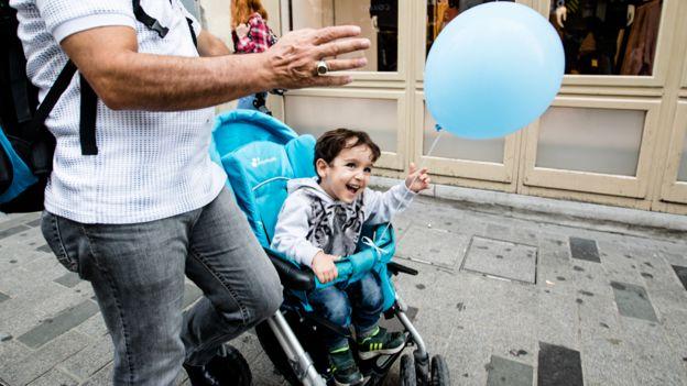 Niño en un carrito de bebé en la calle con un globo