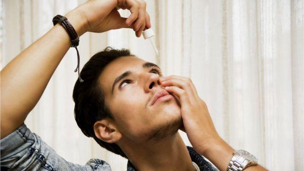 Hombre joven echándose gotas en los ojos.