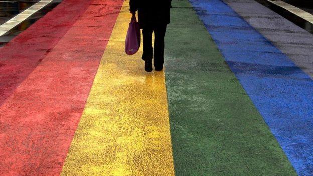 Pessoa anda sob rua pintada com cores do arco-íris.
