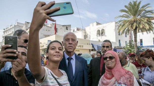 Supporters take pictures with Tunisian presidential candidate Kais Saied