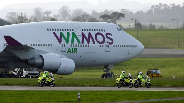 Police officers ride next to the plane