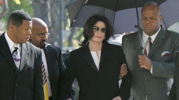 Michael Jackson llega con sus asistentes a un tribunal en Santa Bárbara, California, donde enfrentaba un juicio por abuso sexual en 2005