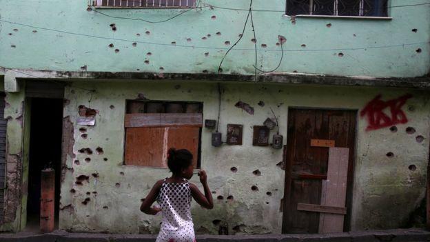 Fachada crivada de balas no Complexo do Alemão, no Rio, em fevereiro