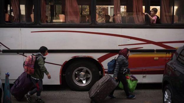 Peruanos varados en Chile caminando con sus valijas frente a un autobús