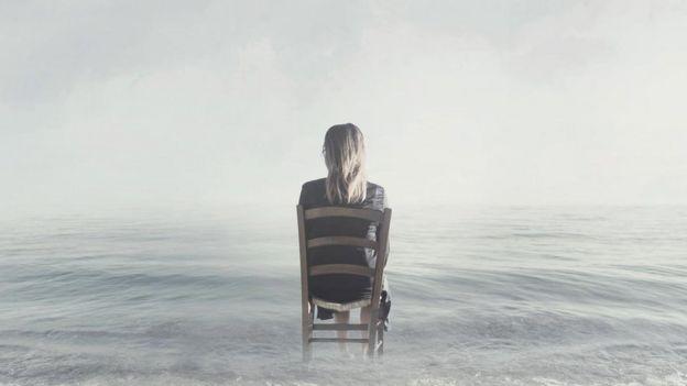 Mujer de espaldas en una silla.