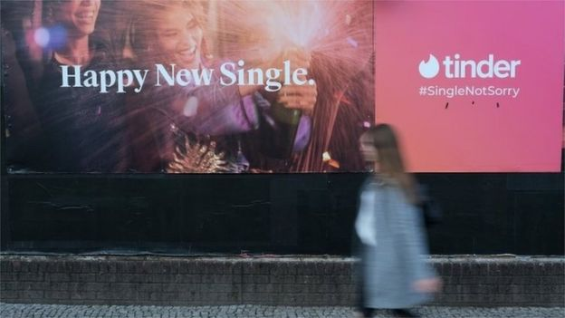 Mulher passa diante de cartaz do Tinder