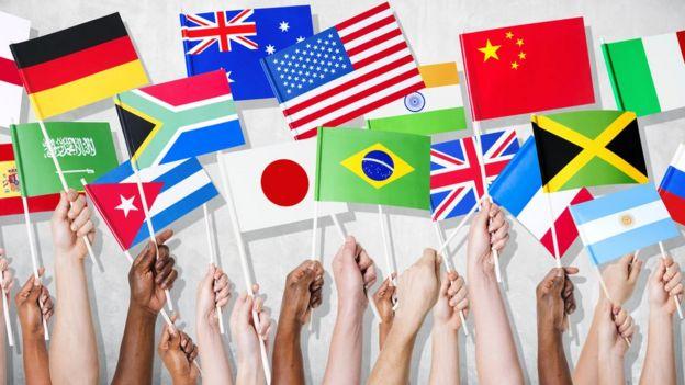 Serie de banderas sostenidas por diferentes personas.