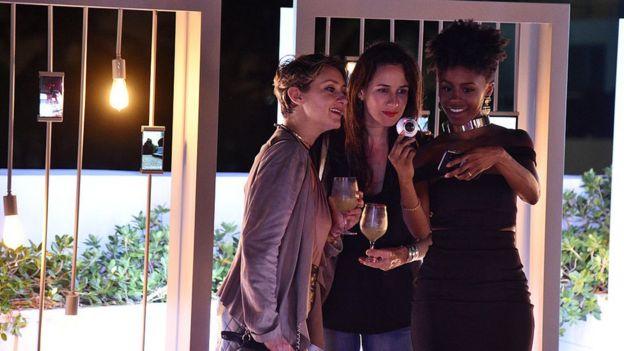 Tres chicas grabando un video con una cámara y viendo el resultado en un celular