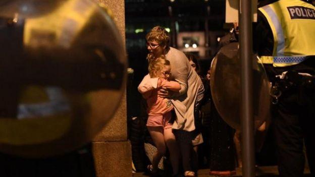Una mujer sostiene a una niña