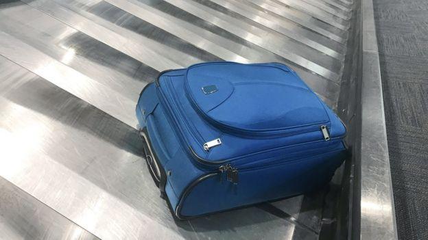Blue case on luggage carousel