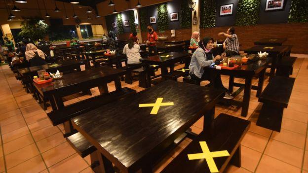 Pengunjung menyantap hidangan di antara meja yang diberi tanda silang di salah satu restoran di Srengseng Sawah, Jakarta Selatan, Kamis (09/04).
