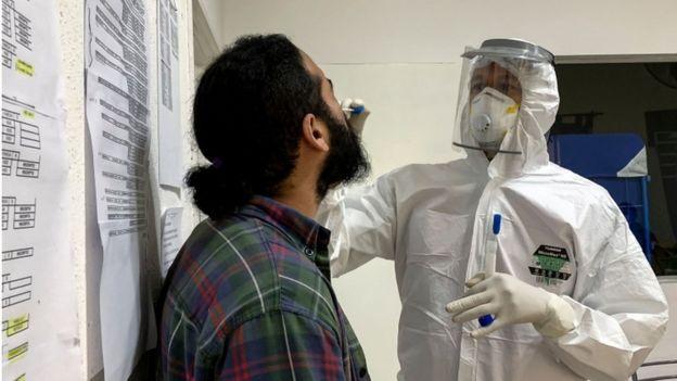 Un médico practica un hisopado nasal