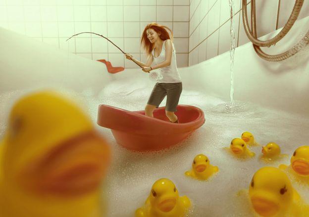A woman fishing in a bathtub