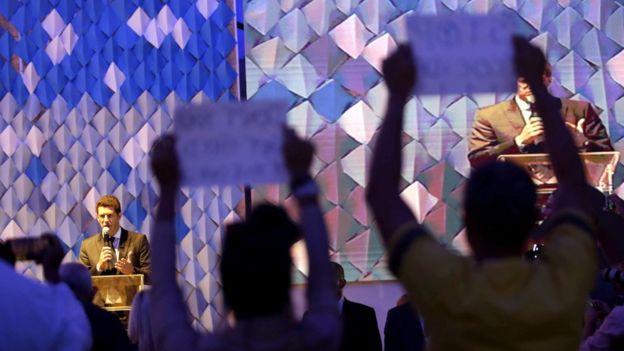 No plano de fundo, o ministro Ricardo Salles aparece falando no microfone; na plateia, duas pessoas levantam cartazes em protesto
