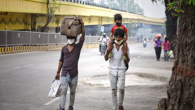 Two men walking, one carrying a bag and the other a child