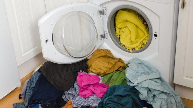 ropas numa máquina e no chão