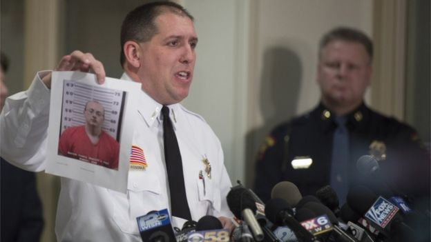 Baron County Sheriff Chris Fitzgerald holds up a photo of the suspect