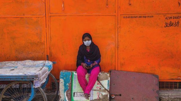 Una mujer india con una mascarilla en una calle desierta.