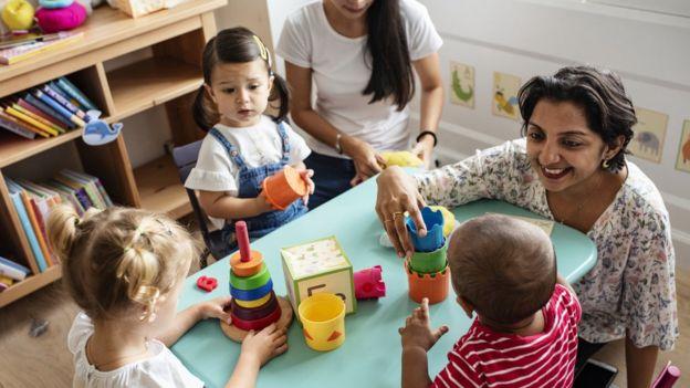 Crianças brincando com uma professora na sala de aula