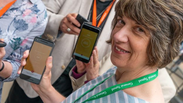 The Bishop of Gloucester, Rt Revd Rachel Treweek, holding a phone showing the app
