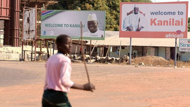 A person walks past boards bearing pictures of Yahya Jammeh in his home town of Kanilai, The Gambia - 22 January 2017