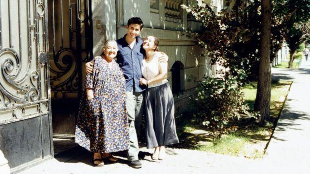 Luis Recabarren na calçada de um imóvel abraçado com a avó Ana González e a tia Patricia