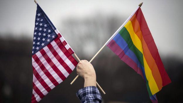 ผู้ประท้วงถือธงชาติสหัฐฯ และธงสีรุ้ง ระหว่างการเดินขบวนมิลเลียนวูแมน ในกรุงวอชิงตัน ม.ค. 2017