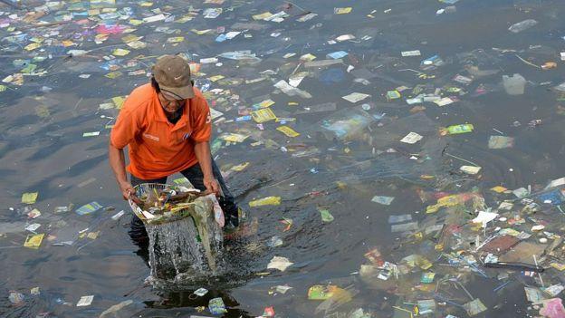 Homem coleta plástico das águas do mar nas Filipinas