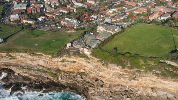 Vista aérea mostra parte costeira, casas e uma estação de tratamento de esgoto