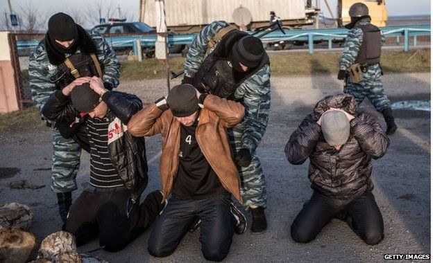 Pro-Russia armed men search people at Chongar checkpoint blocking the entrance to Crimea on 10 March