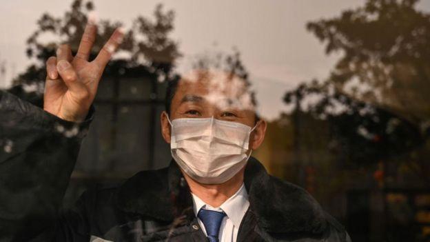 Un guardia de hotel gesticula mientras mira a la cámara en Wuhan, en la provincia central china de Hubei.