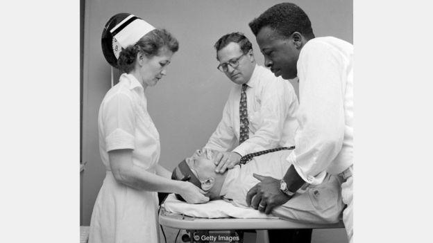 Foto antiguo de neurocirujanos con pacientes.