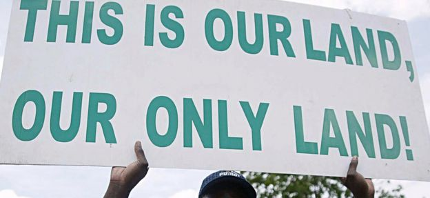 Man holding a sign saying 'this is our land, our only land'