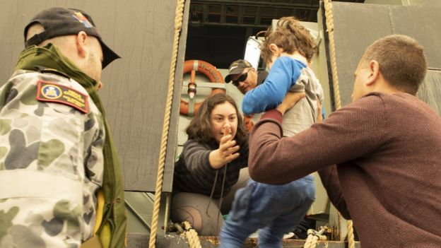 A member of the Australian navy looks on as a child is lifted on board a boat for evacuation from bushfires in Mallacoota, Victoria, 3 January 2020