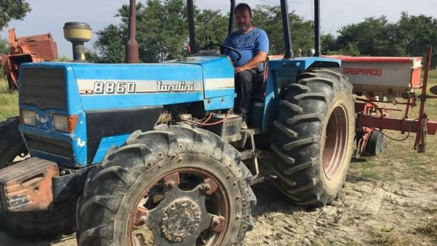 Ronald sits on a blue tractor in his farm.