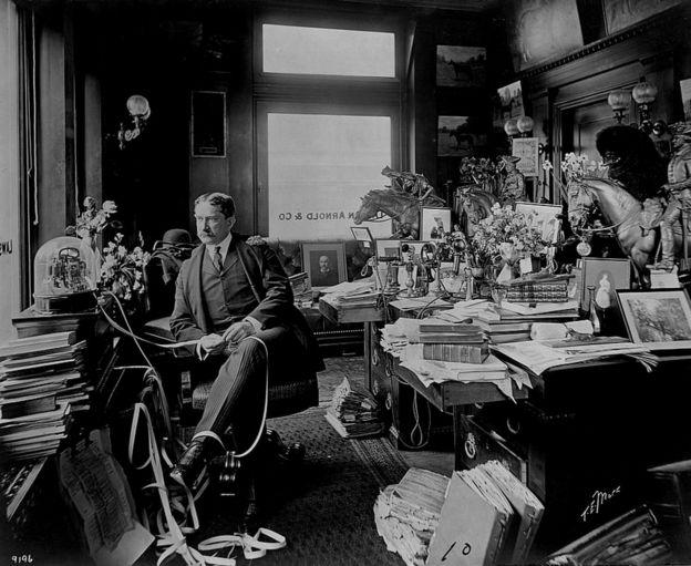El corredor de bolsa Thomas William Lawson sentado frente a una máquina de cinta de teletipo