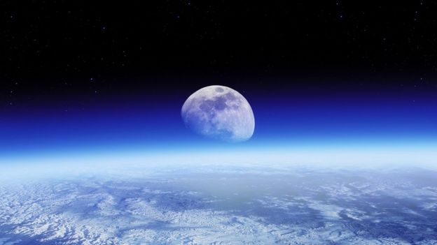 The moon, rising over the earth's surface
