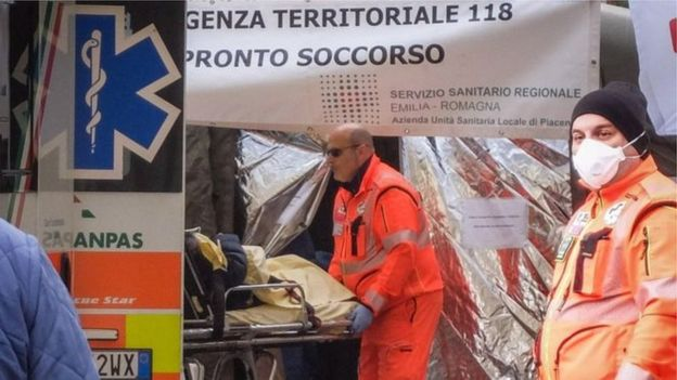 Medical staff transport patients in Italy