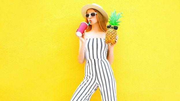 Modèle féminin avec un ananas et une tasse de jus. Elle porte un pantalon rayé blanc et un chapeau rond. Elle est debout sur fond jaune