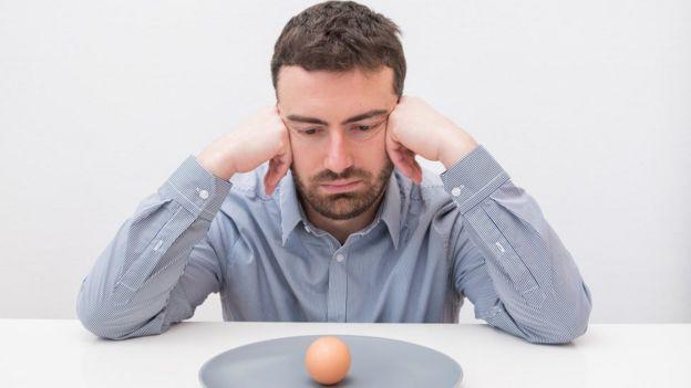 Homem olhando ovo